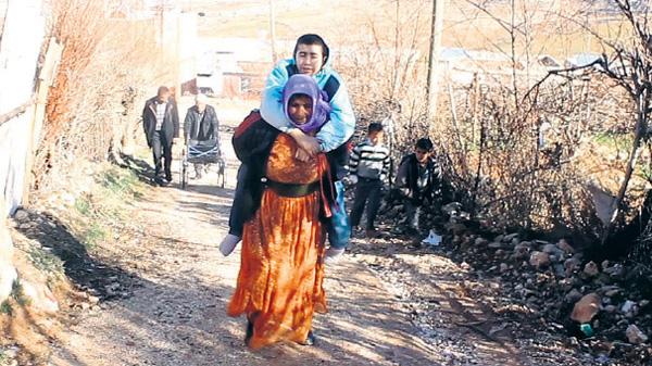 Oğlunu sırtında okula taşıyor